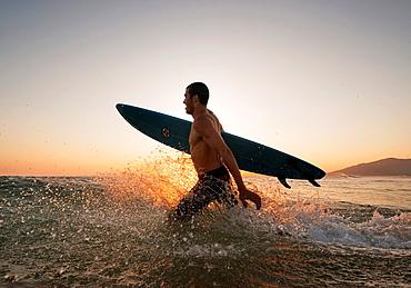 Man running into the sea with a surf board. Tarifa, Costa de la Luz, Cadiz, Andalusia, Spain, Europe.
