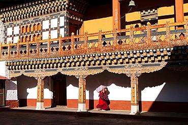 A buddhist monk carrying provisions at Punakha Dzong, Punakha, Bhutan, Asia.