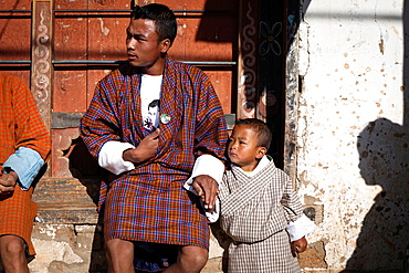 Man and son in traditional dress, a village of Punakha Valley, Bhutan, Asia.