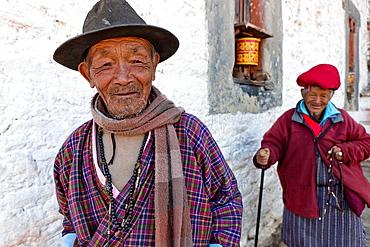 Two old men circling Jampa Lhakhang Temple, Jakar, Bumthang, Bhutan, Asia.