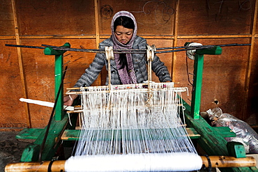 Girl working at a loom weaving a carpet, Bumthang, Bhutan, Asia.