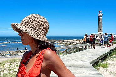 woman look at the sea close to a lighthouse in San Ignacio town, Uruguay
