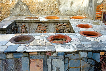 A thermopolium was the equivalent of a modern day cafe/bar where Hot and cold food was sold from an L shaped masonry counter containing terracotta vessels, archeological site of Pompeii, province of Naples, Campania region, southern Italy, Europe