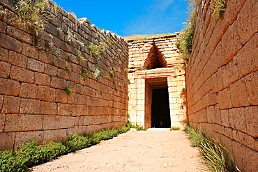 Entrance to the Treasury of Atreus is an impressive 'tholos' beehive shaped tomb on the Panagitsa Hill at Mycenae The entrance has the typical square 2 upright jams covered with a lintel that weigts around 100 tons Above the door is a trangular 'False' or corbel arch Mycenae UNESCO World Heritage Archaeological Site, Peloponnese, Greece