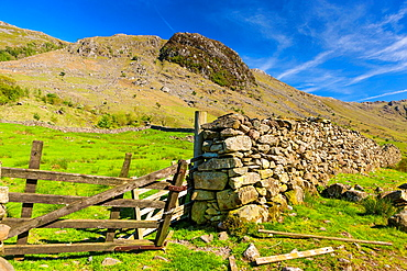 Old gate to field with Hind Crag in the background, near Seathwaite, Lake District National Park, Cumbria, England, Europe
