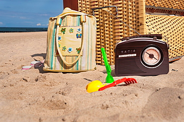 A beach chair, alongside are a radio, a beach bag and beach toys at the beach from the baltic resort Kuehlungsborn, biggest seaside resort of Mecklenburg, administrative district Bad Doberan, Mecklenburg-Western Pomerania, Germany, Europe