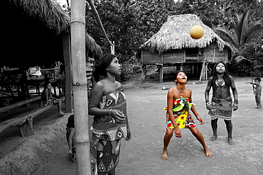 young girls playing football on a village's square of Embera native community living by the Chagres River within the Chagres National Park, Republic of Panama, Central America