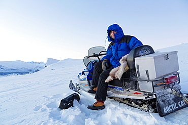 White man sitting on snowmobile at sarek national park with mount Skerfe in the background in winter time