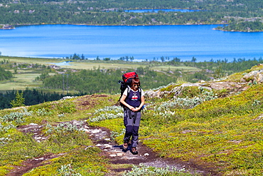 Woman hiking in mountain area in Swedish lapland with lake vassijaure in background