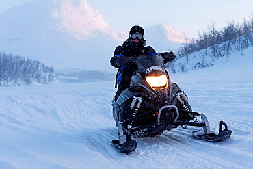 Man driving snowmobile in mountain area in Swedish lapland