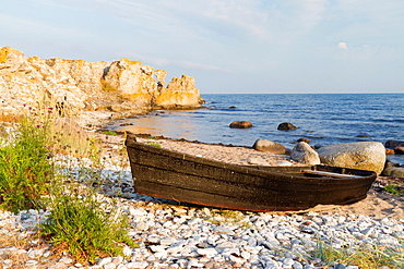 Old rowboat laying at shore of coast line in Gotland, sweden