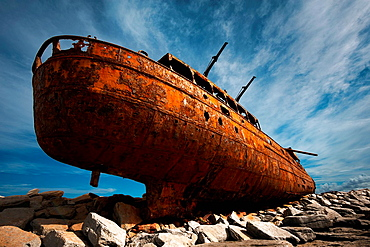 Rusted shipwreck on rocky beach