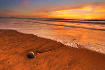 Rock washed up on beach at sunset