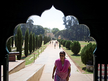 View of people walking on treelined path through an arched structure, Srirangapatna, Karnataka, India
