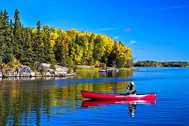 A northern Manitoba landscape of fall foliage color and reflections in a small lake at Baker Narrows near Flin Flon, Manitoba, Canada