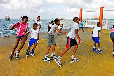 Group Of Kids Going Rollerblading Near The Port Of Colon, Republic Of Panama, Central America