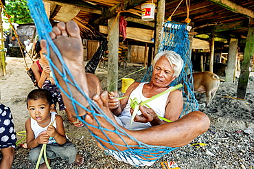 Philippino family resting underneath their house, Cuyo island, Philippines, Asia