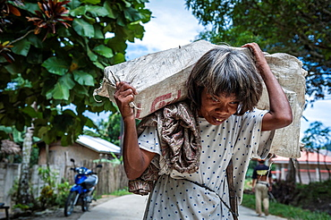 Woman carrying a heavy load on her shoulders, Port Barton, Philippines, Asia