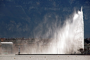 200 meters high famous Jet d'Eau fountain on Geneva Lake, Lac Leman, powered by jet engine, buildings of town of Geneva in the background, Saleve mountain in backgroung behind buildings, Switzerland, Europe