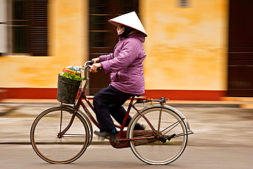 Woman cycling, Ninh Binh, Vietnam