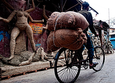 Bicycle passing by an efficy workshop in kumartuli distric Calcutta, West Bengal, India