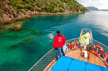 Tourists on the walking yacht look at ruins of the sunk city Kekova, Turkey