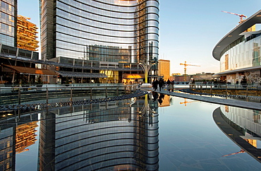 people walk among the ponds reflecting cool buildings at business hub, on the edge Christmas trees
