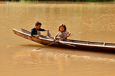 Lanten girl and boy in their dugout canoe on the Nam Ha River, Luang Nam Tha, Laos