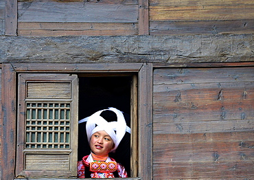 A Long Horn Miao girl looking out the window of her home
