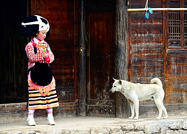 A Long Horn Miao girl standing by her home with her dog