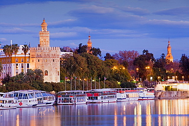 Gold tower in Guadalquivir river In the background towers of Espana square Seville, Andalusia, Spain