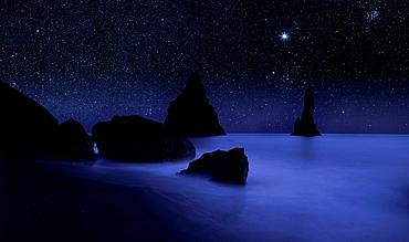 Starry night sky and Reynisdrangar cliffs, South Coast, Iceland digital composite
