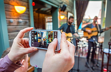 Using a smart phone to photograph a small band during the Winter Lights Festival, Reykjavik, Iceland
