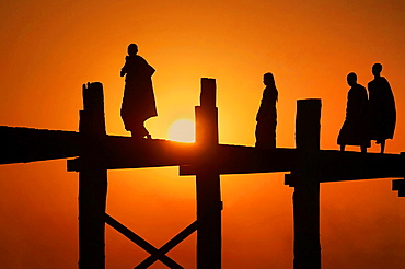 Silhouette of monks on U Bein bridge at sunset. Myanmar, Mandalay, Amarapura, U Bein