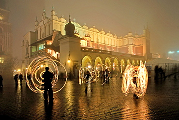 fire juggling in front of the Sukiennice Cloth Hall in mist, Main market square, Krakow, Poland, Central Europe