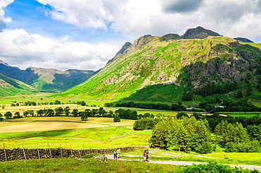 Walkers in the Langdale valley with Langdale Fell and Mickleden valley in the distance. Lake District, Cumbria, England.