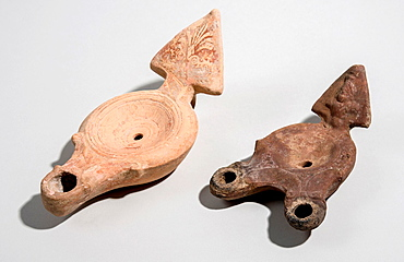 Two Roman era terracotta oil lamps 1st century CE one nozzle on the left and two nozzle sample on the right.