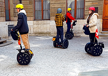 new way of touristic sightseeing on Segway, two-wheeled, self-balancing electric vehicle invented by Dean Kamen, Geneva, Switzerland, here the group of tourists in courtyard of townhouse.