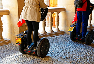 new way of touristic sightseeing on Segway, two-wheeled, self-balancing electric vehicle invented by Dean Kamen, Geneva, Switzerland, here tourists visiting building of townhouse.
