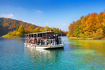 Croatia, autumn landscape of Plitvice Lakes National Park, electric power ferry boat with tourists on the lake, Plitvice, central Croatia.