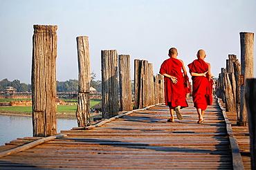 Two young monks crossing U Bein bridge. Myanmar, Mandalay, Amarapura, U Bein.