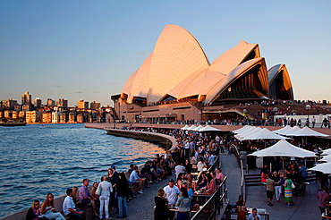 Last rays of the sun on Sydney Opera House, many people drinking and eating at restaurants and bars with outdoor seating. Australia, New South Wales, Sydney.