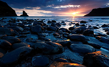 The sun sets over the dark boulders at Talisker Bay in the Highlands of Scotland.