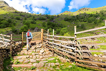 Female hiker approaches the footbridge thats leads towards Sour Milk Gill, Seathwaite in the Lake District.