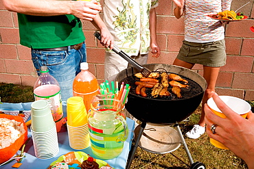 Man cooking with friends at barbecue