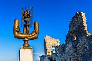"Europe, France, Vaucluse, Luberon. The perched village of Lacoste. Sculpture of Alexander Burganov ""The Marquis de Sade"" dedicated to Pierre Cardin in front of the ruins of the castle of the Marquis de Sade."