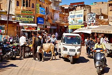 Jaisalmer street scene with cow, tuk tuk and motorbike, Jaisalmer, Rajasthan State, India.