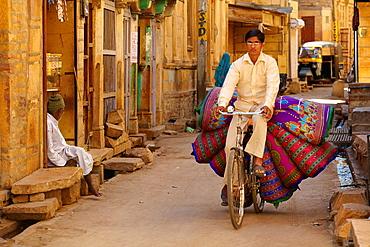 Jaisalmer street scene with indian man on the bicycle, Jaisalmer, Rajasthan State, India.