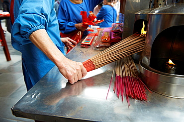 A Temple functionary lighting a large bundle of incense on fire at the Hsingtian Temple.