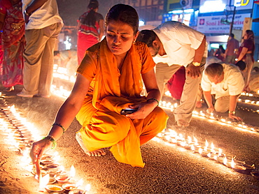 Indians light oil lamps in the street for a Hindu festival in Bangalore, Karnataka, India.